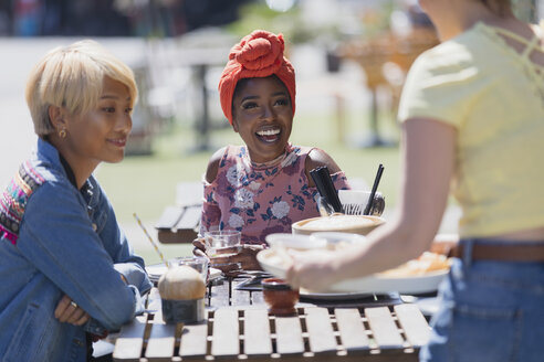 Young women friends enjoying lunch at sunny sidewalk cafe - CAIF22708