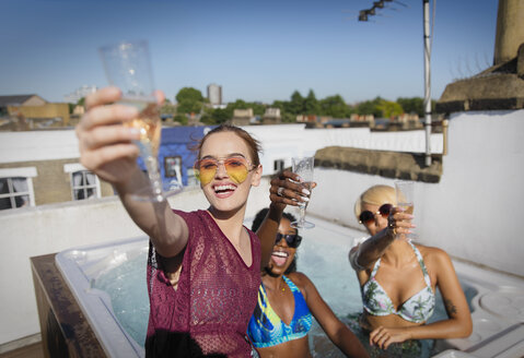 Portrait confident, carefree young women friends drinking champagne in sunny rooftop hot tub - CAIF22720