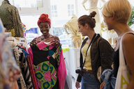 Young woman friends shopping in clothing store - CAIF22738