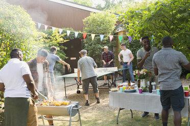 Male friends playing ping pong, enjoying backyard barbecue - CAIF22747