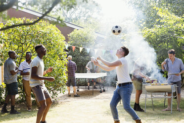Male friends playing soccer and ping pong, enjoying backyard barbecue - CAIF22750