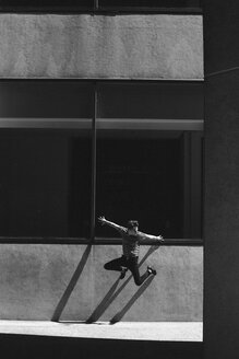 Exuberant young man jumping against urban wall - CAIF22777