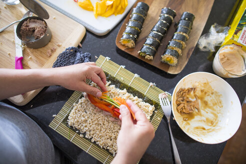 Midsection of woman making sushi on kitchen island at home - CAVF61080