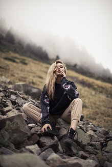 Low angle portrait of woman sitting on rocks against sky in forest during foggy weather - CAVF61104