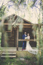 Portrait of newlywed couple standing in porch at forest - CAVF61119