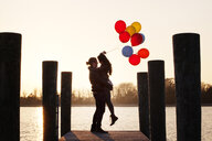 Man lifting woman while holding balloons on pier during sunset - CAVF61152