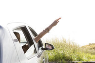 Woman waving hand through window while traveling in car against clear sky during sunny day - CAVF61161