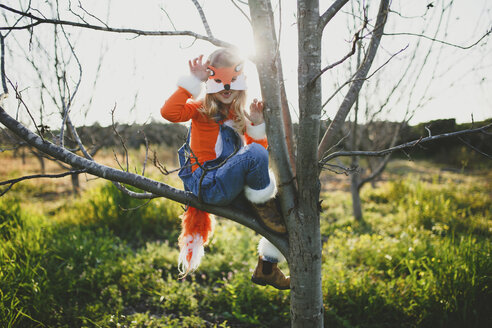 Portrait of girl in fox costume sitting on bare tree against sky during Halloween at park - CAVF61185