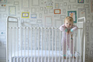 Portrait of cute baby girl leaning on railing while standing in crib against wall at home - CAVF61218