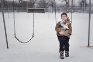 Portrait of boy with dog sitting on swing at playground during winter - CAVF61224