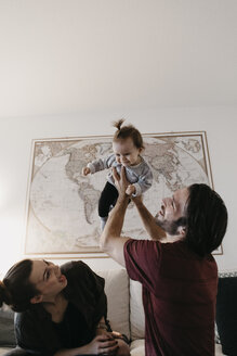 Happy family playing with baby girl in living room at home - LHPF00449