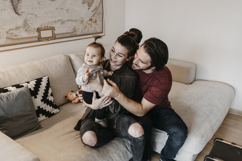 Happy family with baby girl in living room at home - LHPF00452