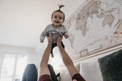 Happy baby girl being lifted up by her father in living room at home - LHPF00455