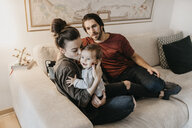 Happy family with baby girl in living room at home - LHPF00458