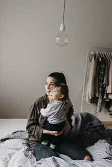 Mother with baby girl sitting on bed at home - LHPF00464
