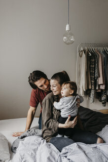 Happy family with baby girl sitting on bed at home - LHPF00467