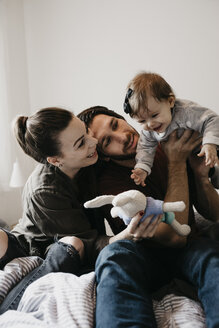 Happy family playing with baby girl on bed at home - LHPF00470