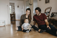 Happy family with baby girl sitting on the floor at home - LHPF00479