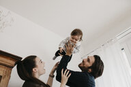 Happy family playing with baby girl at home - LHPF00485