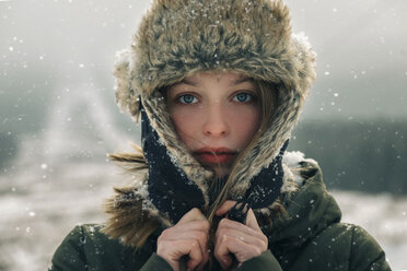 Close-up portrait of woman in warm clothing standing outdoors during snowfall - CAVF61312