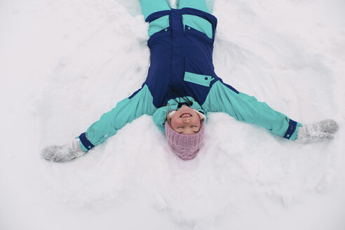 High angle view of woman with eyes closed making snow angel on field - CAVF61336