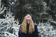 Happy woman with blond hair looking up while standing against trees in forest during winter - CAVF61342
