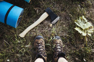 Low section of woman wearing shoes by axe and rolled exercise mat on field in forest - CAVF61363