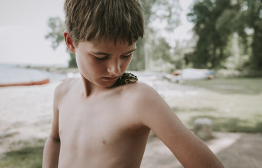 Close-up of shirtless boy looking at frog on shoulder while standing in forest - CAVF61477