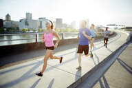 Friends running on bridge against sky in city during sunny day - CAVF61528