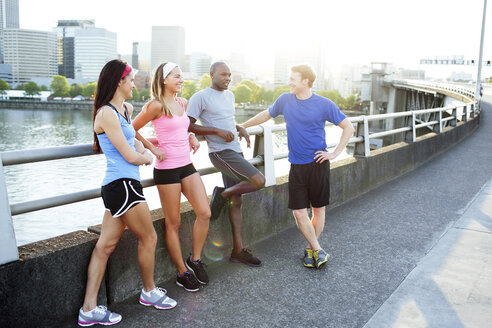 Athlete friends talking while standing on footbridge over river against clear sky in city - CAVF61531