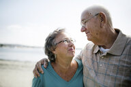 Happy senior couple looking each other face to face while standing at beach against sky - CAVF61540