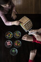 High angle view of siblings making gingerbread house on table at home - CAVF61555