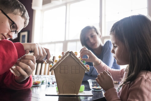 Siblings making gingerbread house together on table at home - CAVF61558