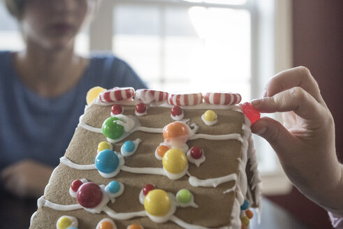 Cropped hand of girl decorating gingerbread house with candies while sister sitting in background at home - CAVF61561