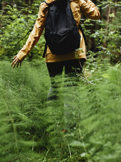 Midsection of female backpacker walking amidst plants in forest - CAVF61573