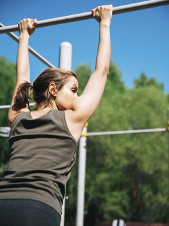 Rear view of woman holding gymnastics bar while exercising at park during sunny day - CAVF61576