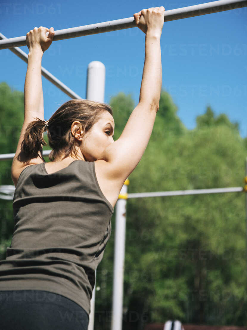 Rear view of woman holding gymnastics bar while exercising at park during sunny day - CAVF61576 - Cavan Images/Westend61