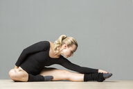 Blond woman doing stretching exercises on the floor - VGF00219