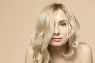 Portrait of naked blond woman in front of beige background - VGF00225