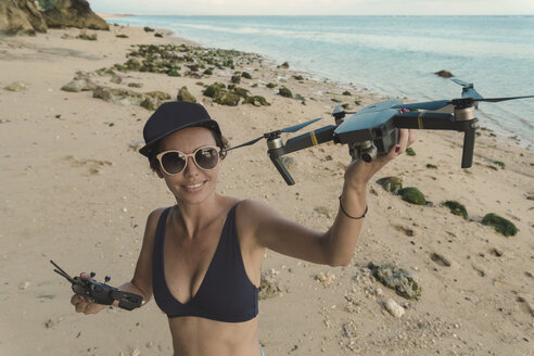 Indonesia, Bali, Nusa Dua, woman holding drone at the beach - KNTF02709