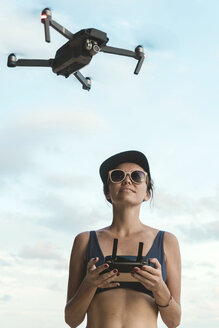 Woman flying drone under sky with clouds - KNTF02712