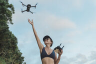 Indonesia, Bali, Nusa Dua, woman flying drone at the beach - KNTF02715
