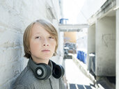 Close-up portrait of boy with headphones standing by wall - CAVF61599