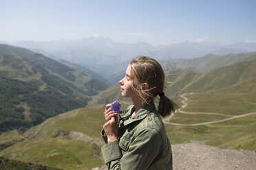 Side view of woman with eyes closed holding flower while standing on mountain against sky during sunny day - CAVF61608