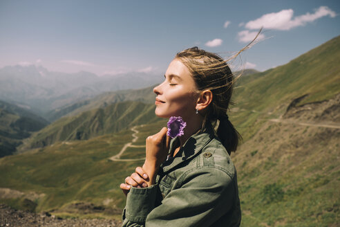 Side view of smiling woman with eyes closed holding flower while standing on mountain against sky during sunny day - CAVF61611