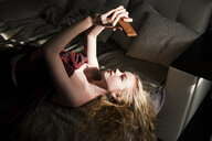 High angle view of woman in off shoulder dress taking selfie with smart phone while lying on bed at home - CAVF61620