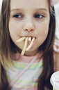 Close-up of playful girl holding French fries in mouth at restaurant - CAVF61626
