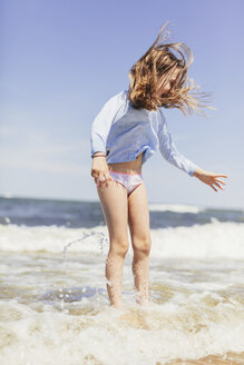 Playful girl jumping in sea on shore against sky during sunny day - CAVF61632