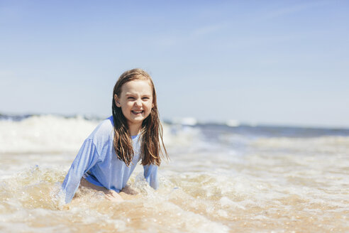 Cheerful girl playing in sea waves against sky during sunny day - CAVF61635
