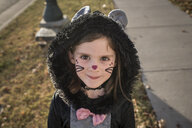 Portrait of cute girl wearing cat costume standing on lawn during Halloween - CAVF61638